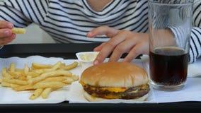 Barnet som ?ter snabbmat, unge ?ter hamburgaren i restaurangen, flickan som dricker fruktsaft lager videofilmer
