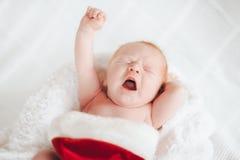 Barnet sover i en hatt av Santa Claus Arkivbild