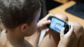 Barnet spelar i ett bärbart modigt konsolsammanträde på en stol hemma arkivfilmer