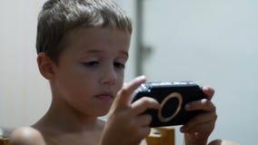 Barnet spelar i ett bärbart modigt konsolsammanträde på en stol hemma stock video