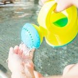 Barnet spelar med bevattna kan i ett inomhus behandla som ett barn pölen Royaltyfria Foton
