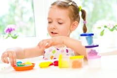 Barnet spelar med färgrik deg Arkivfoton