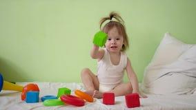 Barnet spelar med mångfärgade kuber på en vit säng och kastar dem till hans moder Bildande leksaker för förträning och stock video