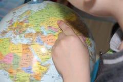 Barnet studerar geografi fingerjordklot som pekar till royaltyfri bild