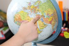 Barnet studerar geografi fingerjordklot som pekar till arkivfoton