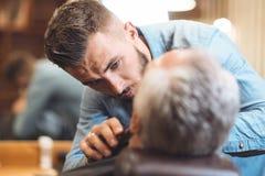 Barnet styr att utforma skägget av klienten i salongen arkivfoto