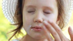 Barnet suddar hans solbränna för fasesolkräm suncream Solskyddskr?m Closeupen behandla som ett barn flickan arkivfilmer