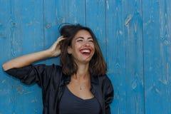 Barnet suntanned kvinnan i en kort överkant och skjorta med härligt modernt smink och hår som poserar mot den blåa träväggen Fotografering för Bildbyråer