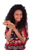 Barnet svärtar den tonårs- flickan för afrikanska amerikanen som äter en skiva av pizz Arkivfoton