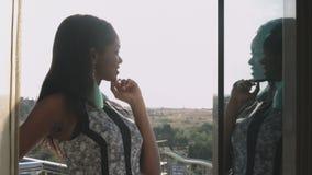 Barnet svärtar flickan i en stilfull klänning står på balkongen och beundrar sikten arkivfilmer