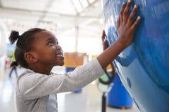 Barnet svärtar flickan som rymmer ett jätte- jordklot på en vetenskapsmitt royaltyfria bilder