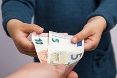 Barnet tar fem och tio eurosedlar Royaltyfria Bilder