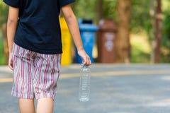 Barnet tar flaskan för att återanvända fack royaltyfria bilder