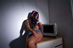 Barnet tatuerade tungt kvinnasammanträde på en tabell som håller ögonen på en tv Royaltyfria Bilder