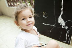 Barnet tecknar en bild av akrylen royaltyfri bild