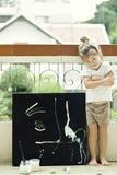 Barnet tecknar en bild av akrylen royaltyfri foto