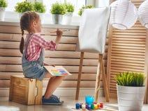 barnet tecknar målarfärger arkivbild