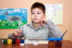 Barnet tecknar målarfärger för en bild royaltyfria foton