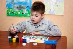 Barnet tecknar målarfärger för en bild royaltyfri fotografi