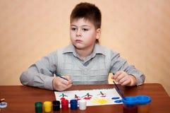 Barnet tecknar målarfärger för en bild arkivbilder
