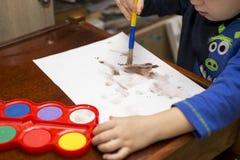 barnet tecknar målarfärger lego för hand för byggnadsbegreppskreativitet upp väggen arkivfoton