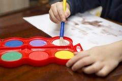 barnet tecknar målarfärger lego för hand för byggnadsbegreppskreativitet upp väggen royaltyfri fotografi