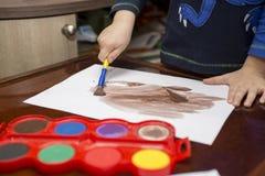barnet tecknar målarfärger lego för hand för byggnadsbegreppskreativitet upp väggen fotografering för bildbyråer