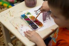 barnet tecknar målarfärger lego för hand för byggnadsbegreppskreativitet upp väggen royaltyfria foton