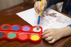barnet tecknar målarfärger lego för hand för byggnadsbegreppskreativitet upp väggen arkivbilder