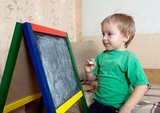 Barnet tecknar på blackboarden med krita royaltyfri foto
