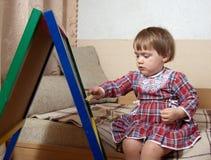 Barnet tecknar på blackboarden med krita royaltyfria foton