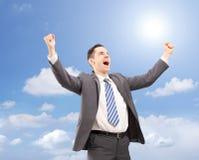 Barnet tillfredsställde affärsmannen som gör en gest lycka mot blå himmel royaltyfri foto
