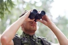 Barnet tjäna som soldat eller jägaren med binokulärt i skog Royaltyfria Bilder