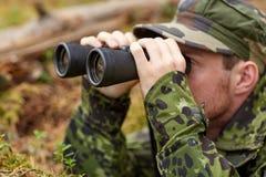 Barnet tjäna som soldat eller jägaren med binokulärt i skog Arkivbilder