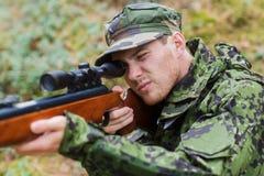 Barnet tjäna som soldat eller jägaren med vapnet i skog Royaltyfri Fotografi