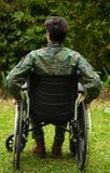 Barnet tjäna som soldat sammanträde på hjulstol på det fria i uteplatsen som trycker på med hans händer hjulen och ger en baksida Royaltyfria Bilder