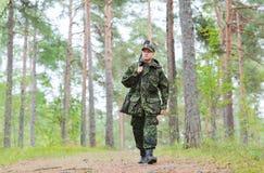 Barnet tjäna som soldat eller jägaren med vapnet i skog Arkivfoto
