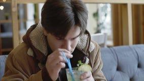 Barnet tröttade mannen som dricker tequila och coctailen i kafét 4K lager videofilmer