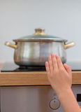 Barnet trycker på den varma pannan på ugnen Fotografering för Bildbyråer