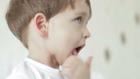 Barnet trycker på hans kanter, då vinkar hans händer, visar glade sinnesrörelser, ler arkivfilmer