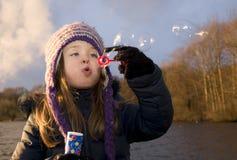 Barnet tycker om att spela med såpbubblor på solnedgången Arkivfoton