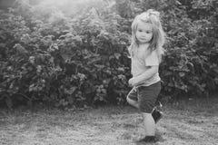 Barnet tycker om barndom pojkebarn med gulligt framsidaanseende på ett ben Arkivbild