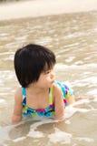 Barnet tycker om waves på strand Arkivbild