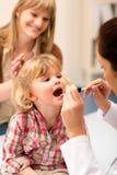 barnet undersöker den pediatriska halsen för den ljusa looken royaltyfria foton