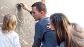 Barnet uppfostrar med deras gulliga liten flickateckning på svart tavla familjgyckel som utomhus har Royaltyfria Bilder