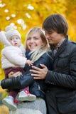 Barnet uppfostrar med dottern på bakgrund av höstskogen Royaltyfri Fotografi