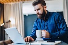 Barnet uppsökte affärsmannen som arbetar på datoren på tabellen som dricker kaffe Mannen analyserar information, framkallar affär Arkivbilder