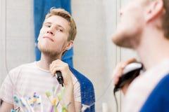Barnet uppsökte den stiliga mannen som har skägget med maskinen i badrummet som ser i en spegel arkivfoto
