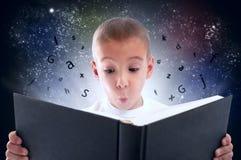 Barnet upptäckte den magiska världen av böcker Arkivbild