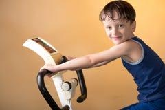 Barnet utbildas på en stationär cykel Sund livsstil royaltyfri foto